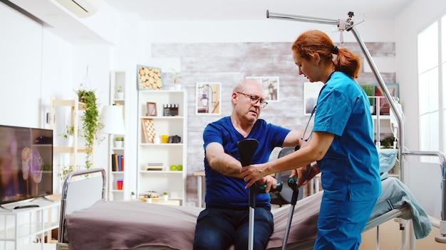Krankenschwester, die einem behinderten alten mann im ruhestand hilft, von seinem krankenhausbett in einem hellen und gemütlichen altenheim aufzustehen