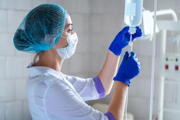 Krankenschwester, die einem patienten einen tropfenzähler für den eingriff im krankenhaus vorbereitet