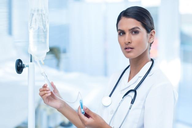 Krankenschwester, die einen intravenösen tropfenfänger anschließt