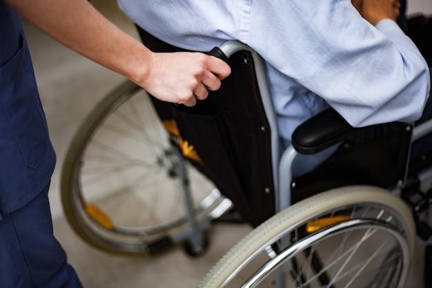 Krankenschwester, die einen verletzten patienten auf einen rollstuhl drückt
