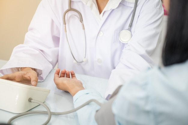 Krankenschwester, die geduldigen blutdruck des pflegeheims nimmt