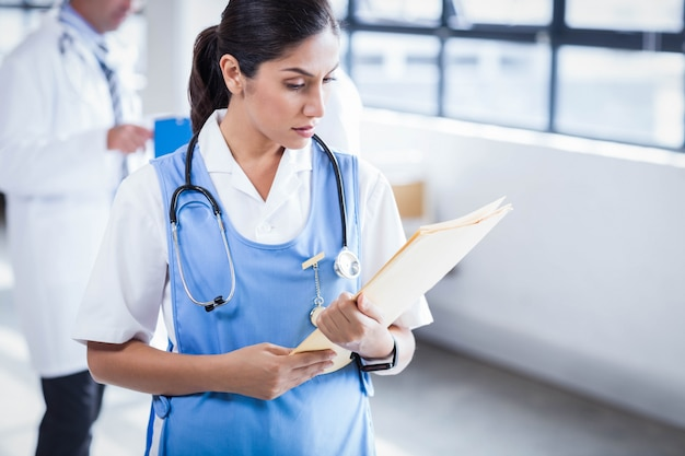 Krankenschwester, die ihre akten im krankenhaus liest
