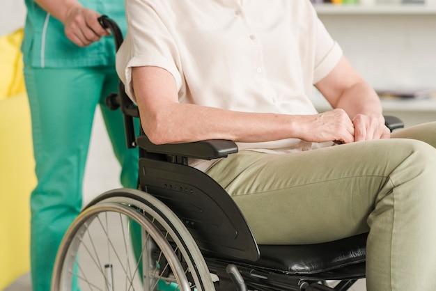 Krankenschwester, die ihrem geduldigen sitzen auf rollstuhl hilft