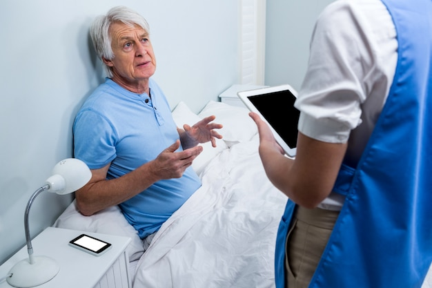 Krankenschwester, die mit älterem mann am krankenhaus sich bespricht