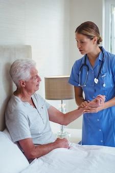 Krankenschwester, die mit älterem mann bei der untersuchung spricht