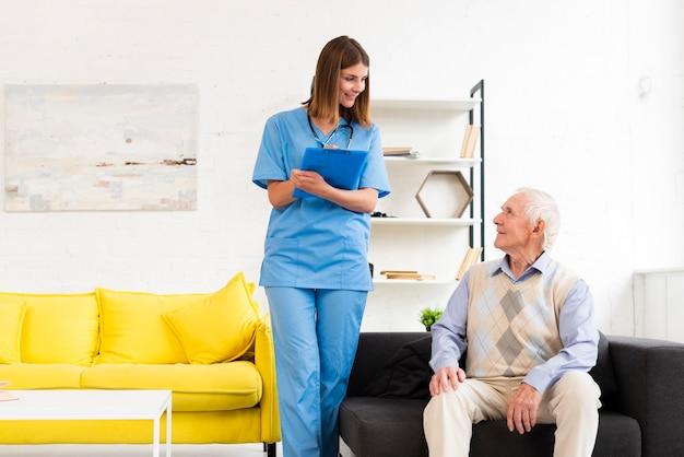 Krankenschwester, die mit dem alten mann sitzt auf schwarzem sofa spricht