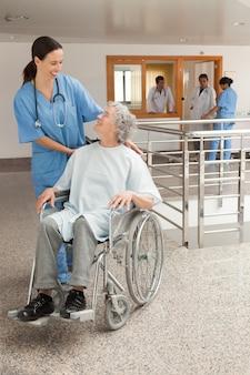 Krankenschwester, die mit den alten frauen sitzen im rollstuhl lacht