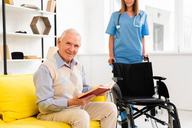 Krankenschwester, die mit einem rollstuhl zu einem alten mann kommt