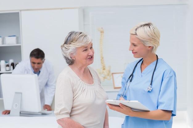 Krankenschwester, die mit patienten während doktor unter verwendung des computers sich bespricht