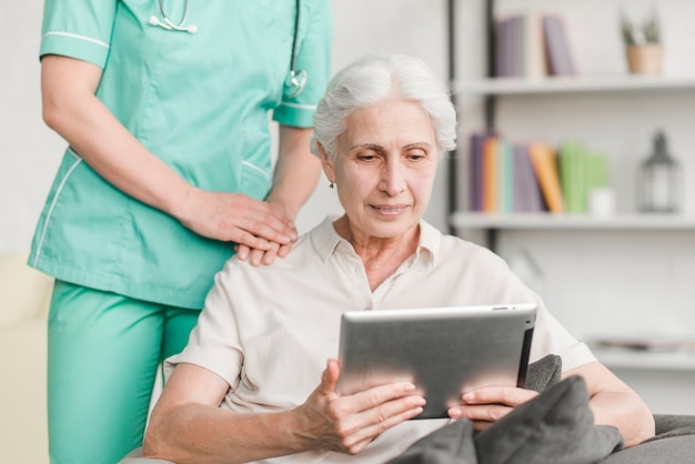 Krankenschwester, die nahe der älteren frau verwendet digitale tablette steht