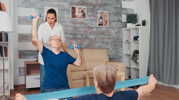 Krankenschwester, die physiotherapie mit älteren paaren tut. haushaltshilfe, physiotherapie, gesunder lebensstil für ältere menschen, training und gesunder lebensstil