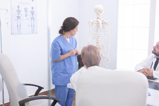 Krankenschwester, die präsentation der menschlichen anatomie am skelett vor ärzten macht. klinik-expertentherapeut im gespräch mit kollegen über krankheit, mediziner