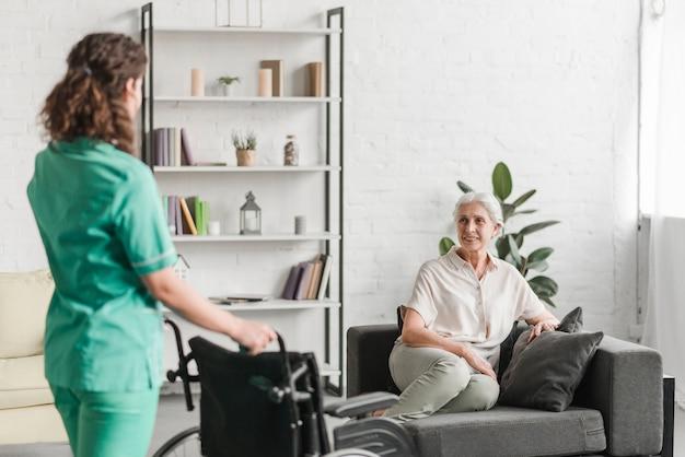 Krankenschwester, die rollstuhl zu ihrem weiblichen patienten des senors bringt, der auf couch sitzt
