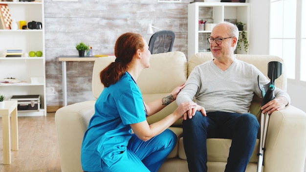 Krankenschwester, die sich um einen alten patienten mit alzheimer-krankheit kümmert, der auf dem sofa in einem hellen pflegeheim mit großen fenstern sitzt