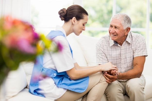 Krankenschwester, die sich zu hause um krankem älterem patienten kümmert