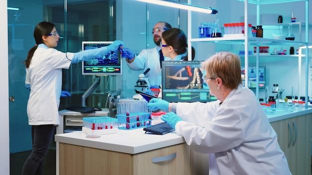Krankenschwester, die tablet-computer mit wissenschaftlichen informationen hält, während chemiker ein mikroskop mit chemischem reagenzglas in der nähe verwendet