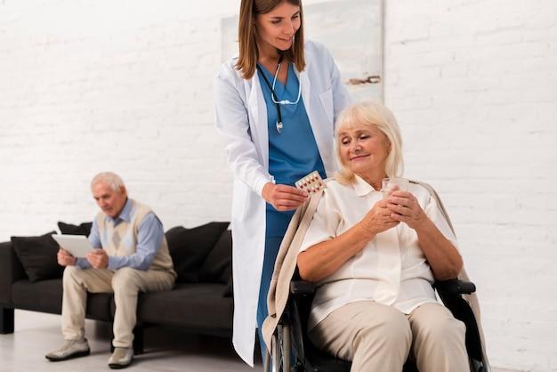 Krankenschwester, die um alter frau sich kümmert