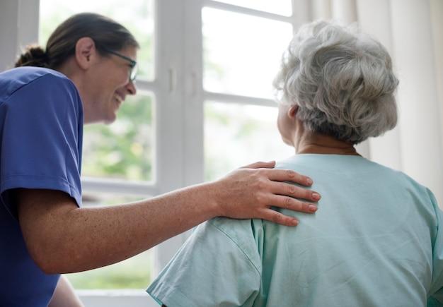 Krankenschwester, die um einer alten frau sich kümmert