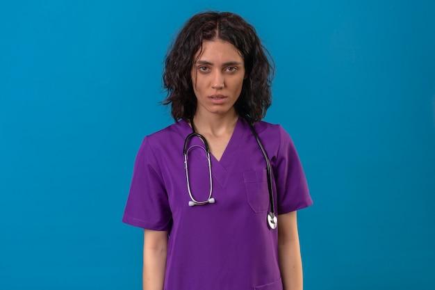 Krankenschwester, die uniform und stethoskop mit ernstem gesicht ohne lächeln trägt, das auf isoliertem blau steht