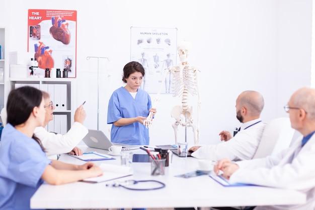 Krankenschwester, die während der präsentation vor ärzten zur untersuchung mit dem menschlichen skelett arbeitet. klinik-expertentherapeut im gespräch mit kollegen über krankheit, mediziner