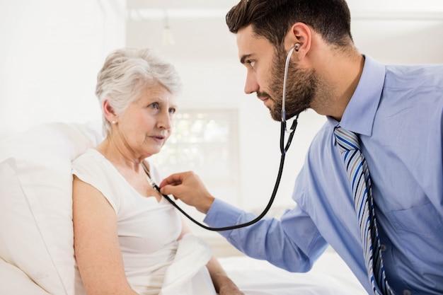 Krankenschwester, die zu hause auf kasten des patienten mit stethoskop hört