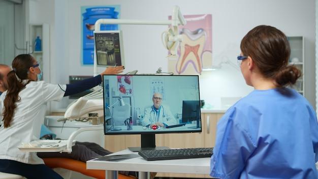 Krankenschwester diskutiert über die beratung mit dem leitenden zahnarzt über videoanrufe in der zahnarztpraxis, während die ärztin mit dem patienten im hintergrund arbeitet. assistent, der sanitäter vor der webcam hört