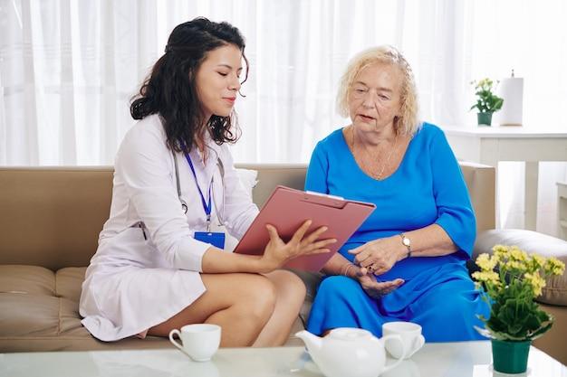 Krankenschwester erklärt älteren patienten das rezept
