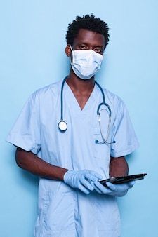 Krankenschwester hält tablet beim blick in die kamera über isoliertem hintergrund