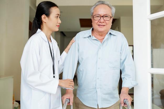 Krankenschwester hilft jungem mann, sich zu bewegen