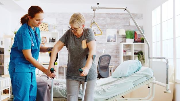 Krankenschwester im altersheim, die einer älteren frau hilft, ihre muskelkraft wiederzuerlangen. physiotherapie und sozialarbeiterin
