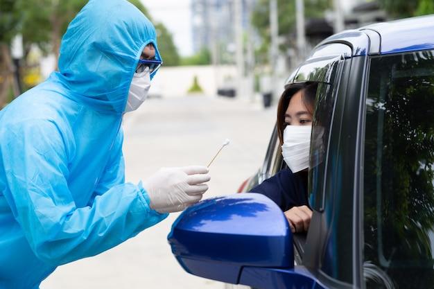 Krankenschwester im psa-anzug oder medizinisches personal in voller schutzausrüstung entnimmt eine probe von einer fahrerin im auto. durchfahrtstest für coronavirus covid-19