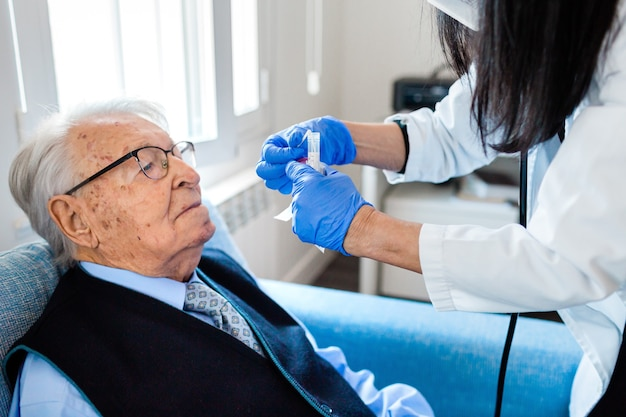 Krankenschwester in blauen damenhandschuhen hebt den kopf eines älteren mannes in blauem hemd und krawatte, um den covid-test durchzuführen, während er zu hause auf der couch sitzt. häusliche krankenpflege.