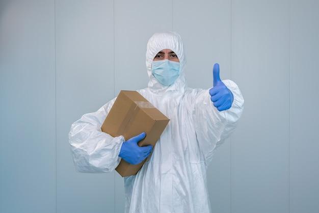 Krankenschwester in einem schutzanzug, die einen daumen nach oben zeigt, nachdem sie während der coronavirus-pandemie eine kiste mit medizinischen hilfsgütern erhalten hat, covid 19. angestellter im gesundheitswesen in einem krankenhaus