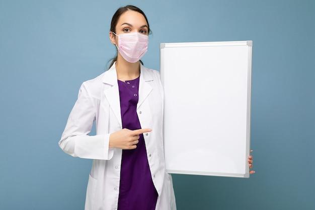 Krankenschwester in schützender gesichtsmaske und weißem medizinischem kittel, die eine leere magnettafel auf blauem hintergrund hält