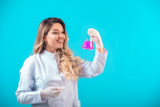 Krankenschwester in weißer uniform, die einen chemischen kolben mit rosa flüssigkeit hält.