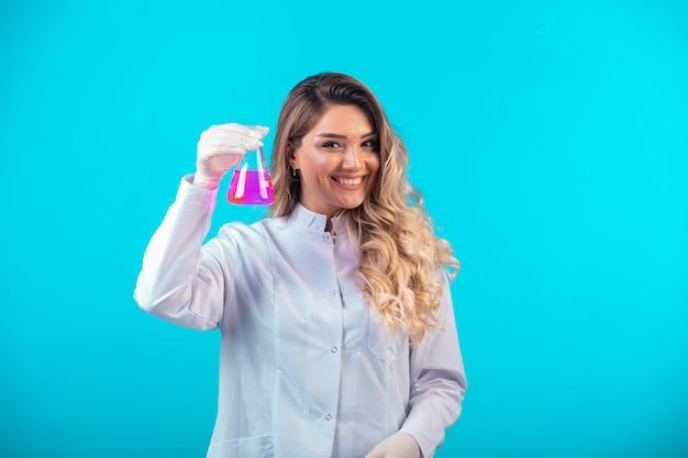 Krankenschwester in weißer uniform hält einen chemiekolben mit rosa flüssigkeit und fühlt sich positiv.