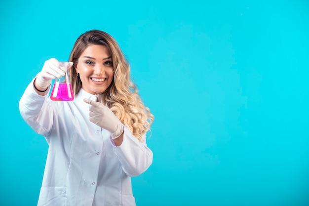 Krankenschwester in weißer uniform hält einen chemiekolben mit rosa flüssigkeit und fühlt sich positiv