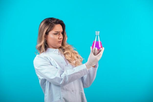 Krankenschwester in weißer uniform hält einen chemiekolben mit rosa flüssigkeit und versucht sich zu erinnern.