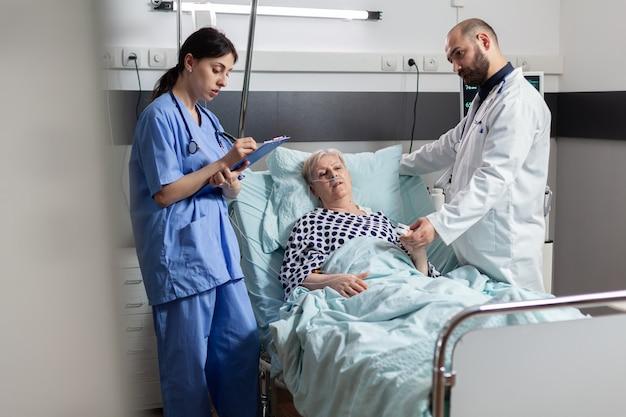 Krankenschwester macht sich während der konsultation der älteren frau notizen in der zwischenablage