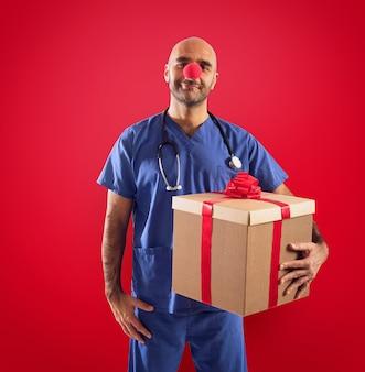 Krankenschwester mit clownnase und großem geschenk auf rotem hintergrund