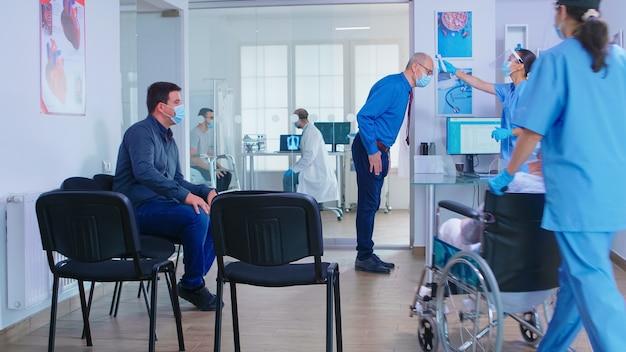 Krankenschwester mit gesichtsmaske für covid-19 im wartebereich des krankenhauses, die die temperatur des älteren mannes mit einem temperaturscanner überprüft. assistent, der einer ungültigen älteren frau im rollstuhl hilft
