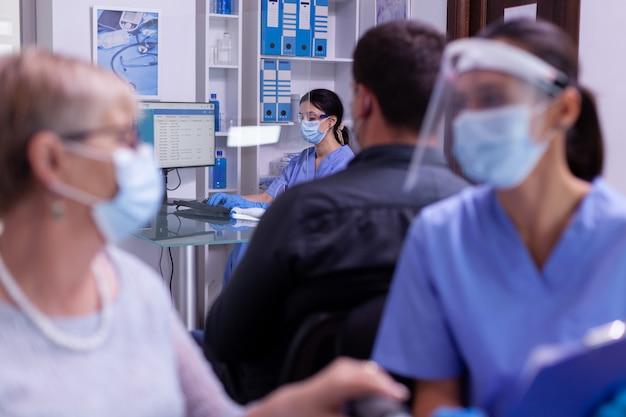 Krankenschwester mit maske, die am computer neue patiententermine tippt