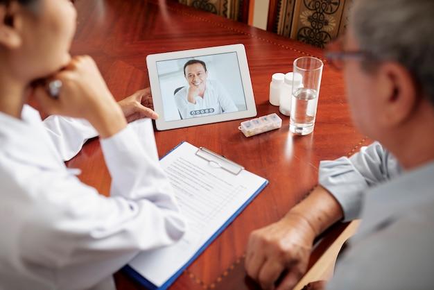 Krankenschwester mit patient haben online-konferenz mit arzt