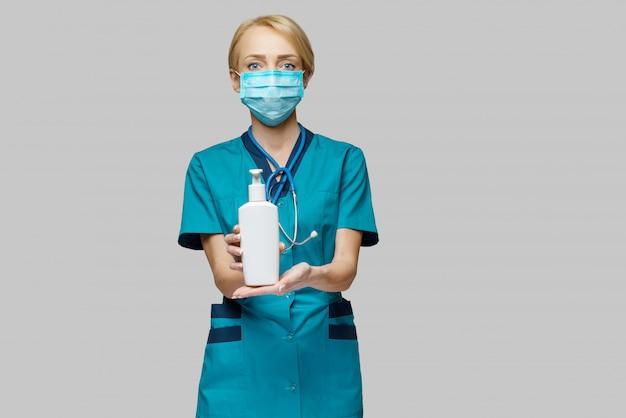 Krankenschwester mit schutzmaske - händedesinfektionsspray oder gel oder flüssigseife