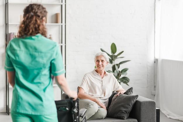 Krankenschwester mit stehender ionenfront des rollstuhls des glücklichen weiblichen patienten