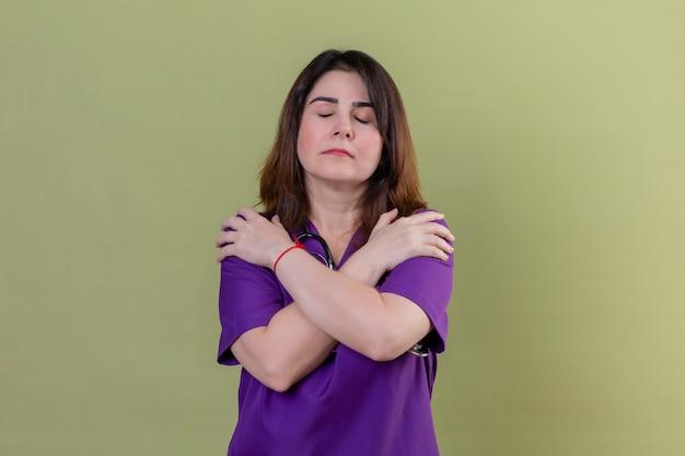 Krankenschwester mittleren alters, die uniform trägt und mit stethoskop sich glücklich und positiv mit geschlossenen augen über grünem hintergrund umarmt