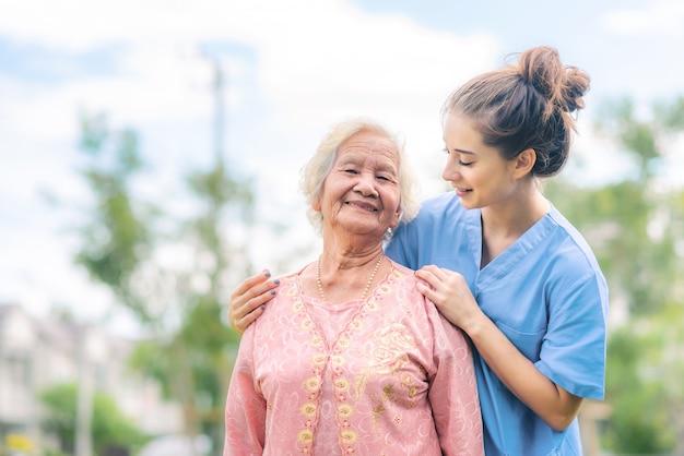 Krankenschwester pflegekraft kümmern sich um asiatische ältere frau im park