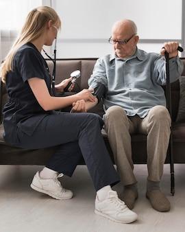Krankenschwester prüft den blutdruck des älteren mannes
