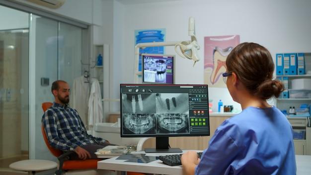 Krankenschwester tippt am computer mit digitalem röntgenbild, während der patient auf den zahnarzt wartet, der auf einem stomatologischen stuhl sitzt. assistent, der mann im beratungsraum einlädt, während er die röntgenaufnahme vom pc analysiert