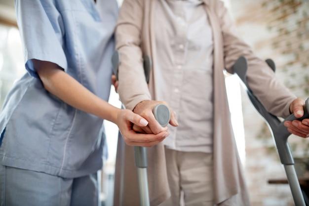 Krankenschwester trägt uniform unterstützende frau mit krücken